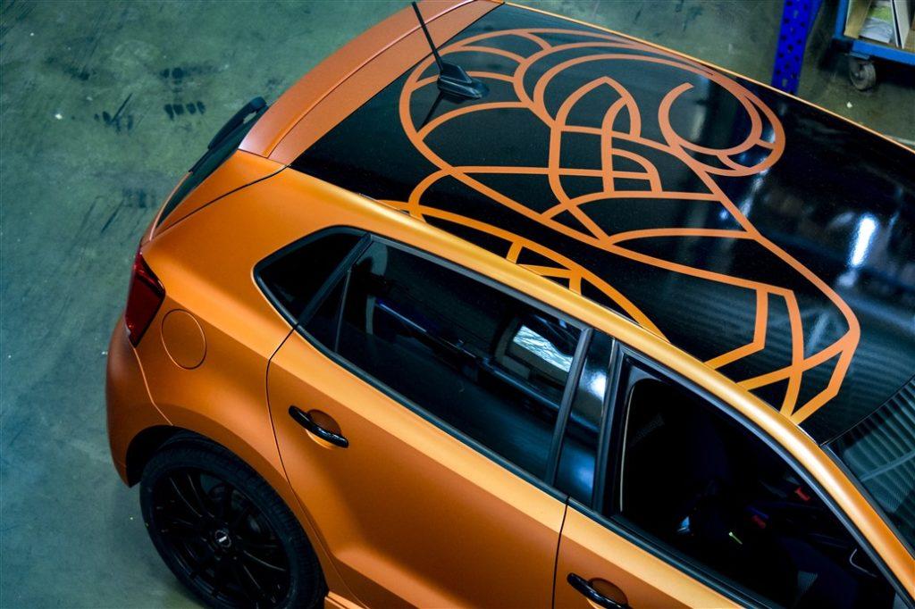 Oranje autowrap met logo op het dak