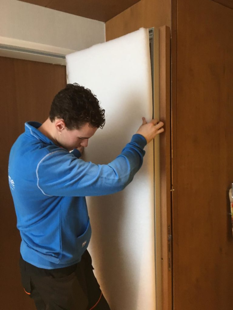 Monteur plaats akoestisch textielframe op binnenkant deur