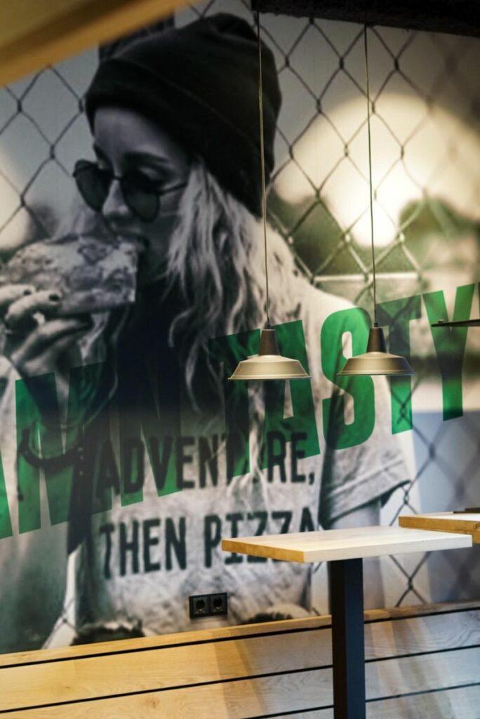 Wandvisual met vrouw die pizza eet en bijschrift 'damn tasty'