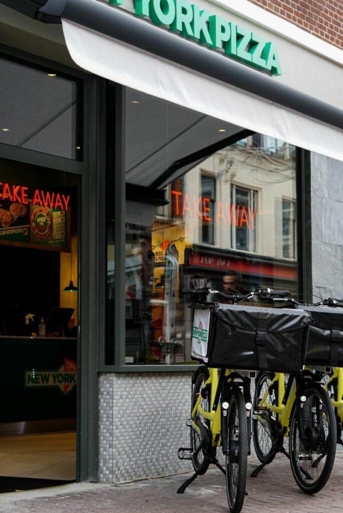 Foto van voorzijde restaurant met gevelreclame en fietsen zichtbaar