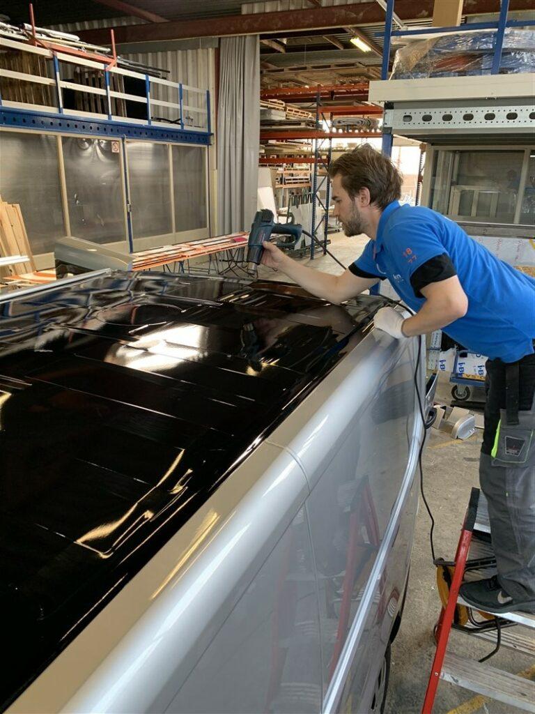 Monteur die een zwarte folie aanbrengt op en grijze bestelwagen