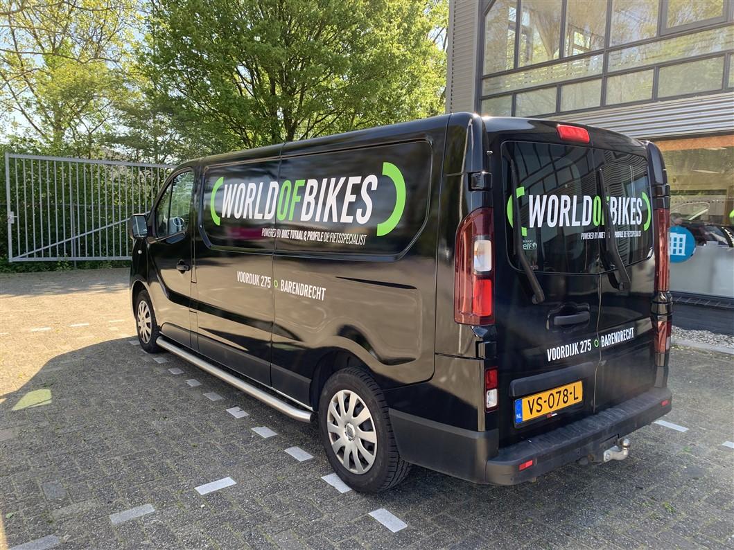 Zwarte gewrapte bestelwagen met wit en groene belettering