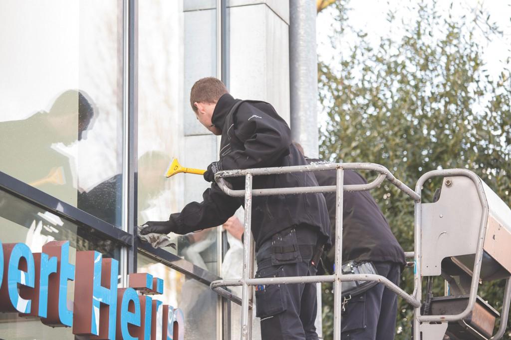 Monteurs die ramen schoonmaken alvorens deze met raamfolie te beplakken