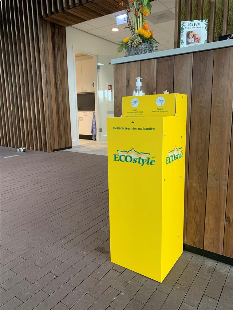 Gele desinfectiezuil met groenkleurige opdruk
