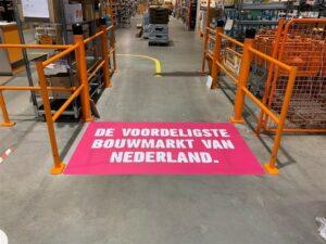Roze vloersticker met opschrift 'de voordeligste bouwmarkt van Nederland'