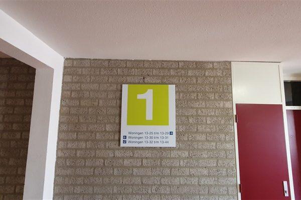 Geel met wit wandbord als aanduiding verdieping 1