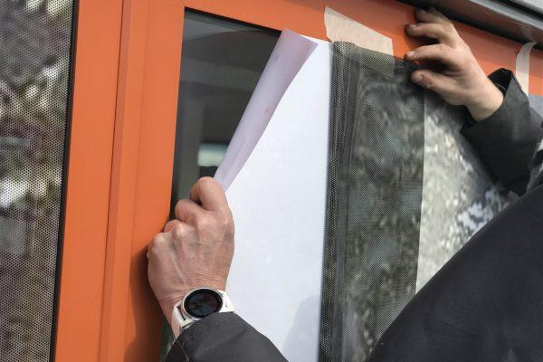 Monteur die bezig is met het aanbrengen van one way vision raamfolie op ruiten van slaapbankencentrum.nl