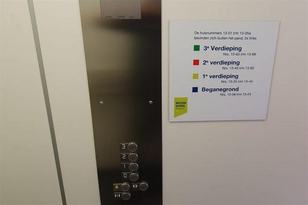 Wandbord in lift Woonzorg Nederland met informatie over indeling verdiepingen