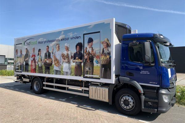 Vrachtwagenreclame bidfood met diverse personen afgebeeld