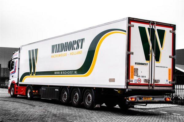 Witte vrachtwagen met geel en groene belettering